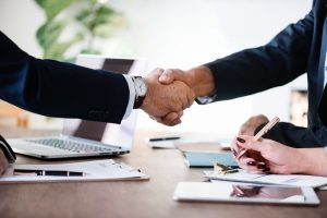 Two people shaking hands over a successful business deal in some of the most flourishing businesses in Miami.