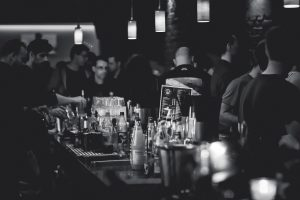 A black and white photograph of a full bar of people talking while the bartenders make their drinks behind the bar.