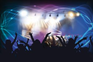 A crowd dancing in front of a music stage at a concert, with lighting and reflectors shining upon them.
