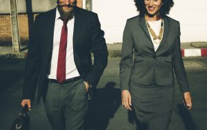 A man and a woman in severe business suits, smiling as they stride towards the camera.