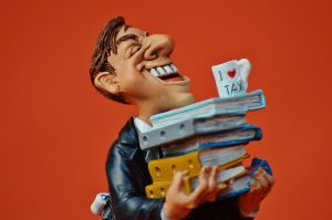 A figurine of a man holding books.