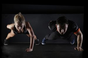Two people doing one-hand push-ups.