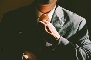 A man in a suit, adjusting his tie.