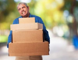 man struggling with boxes, picture showing why you need professional movers
