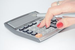 A woman using a calculator to calculate the costs of moving to Florida.