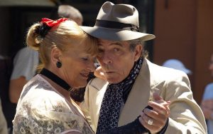 An elderly couple dancing tango cheek to cheek.