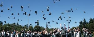 Many successful graduates throwing ceremonial hats in the air.
