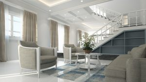 Light gray and white living room with white stairs going to the top floor of the house.