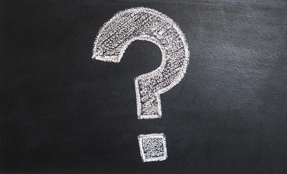 A white question mark on a black board.