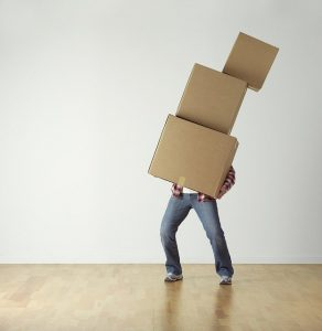 A man carryng a pile of cardboard boxes.