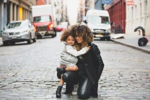 Mother and daughter posing together on a street.