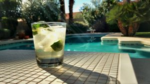 A refreshing drink with lime and ice placed next to a house pool.