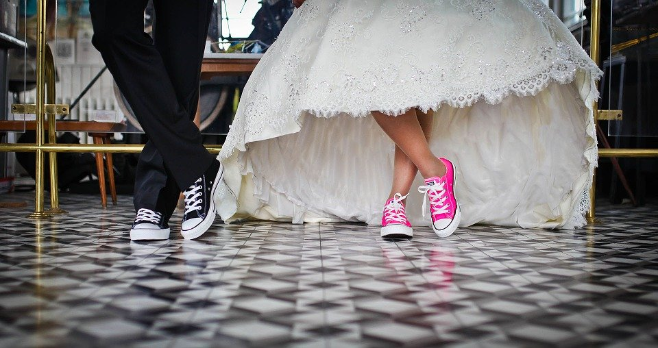 bride and groom wearing sneakers with their wedding outfits.