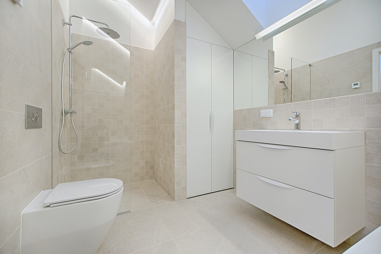 A white and beige bathroom after converting a tub into shower