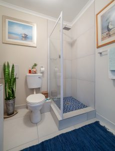 A bathroom with a small doorless shower.