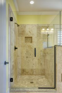 A beige shower with a glass door.