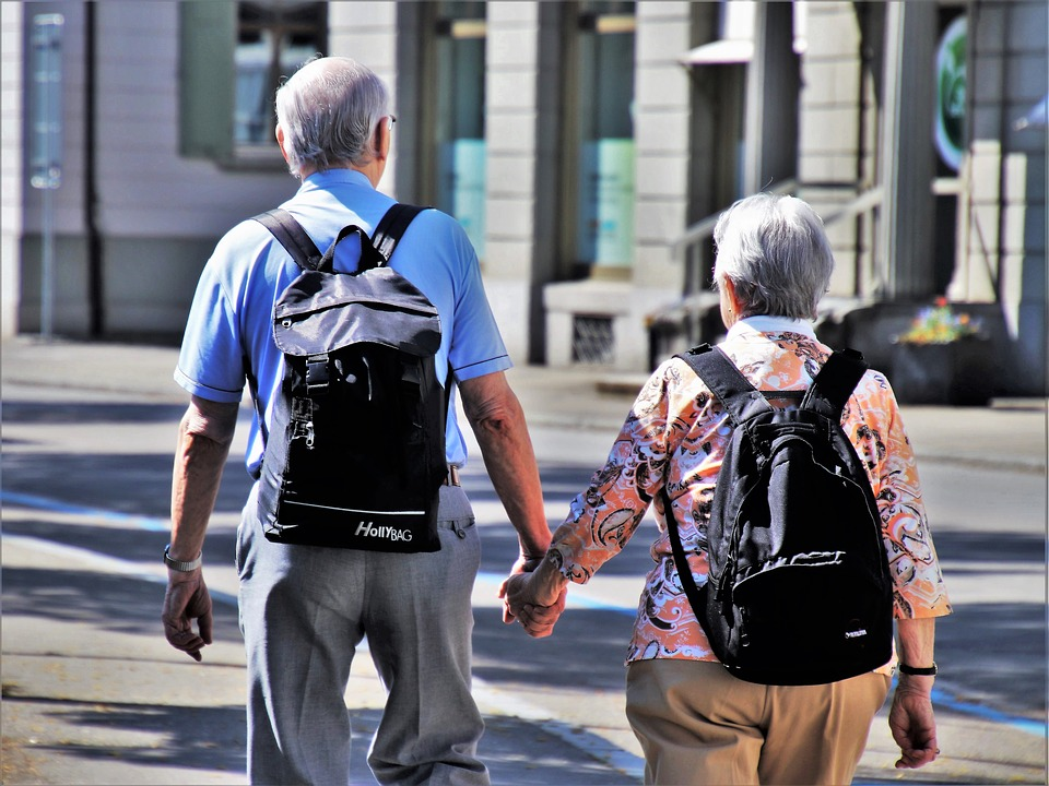 A couple of elderly people holding hands and walking.