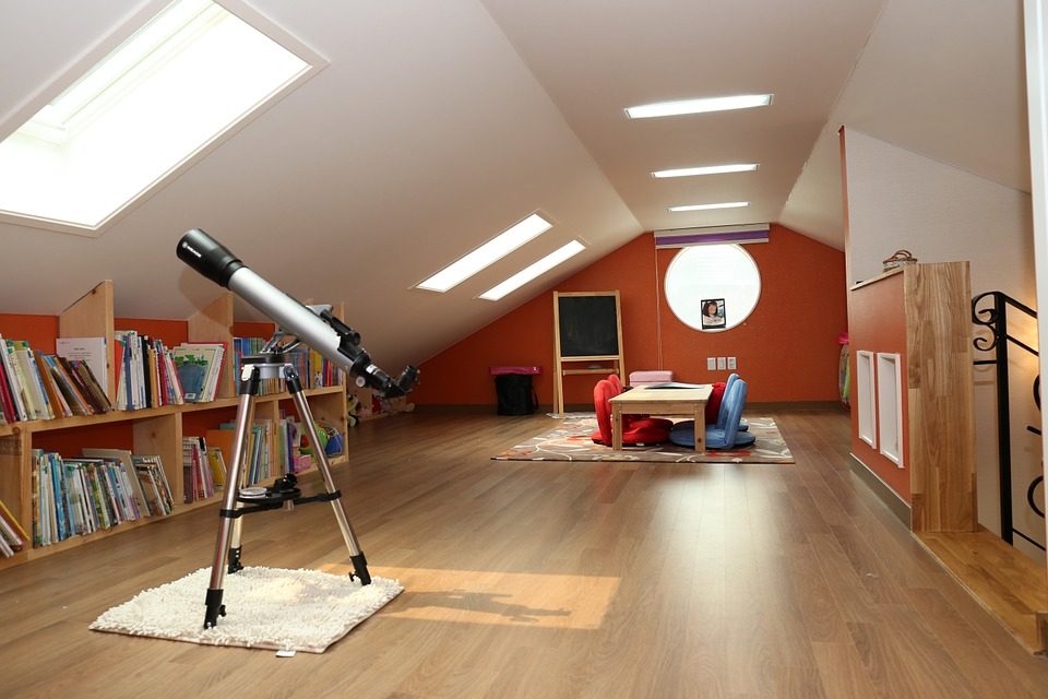 Attic with a lot of natural light and wooden floors.