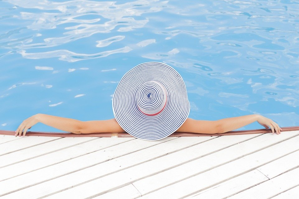 A woman chilling in the pool while wearing a glamorous hat.
