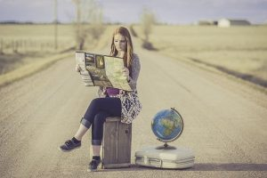 Woman on the road with the suitcase, map, and globe.