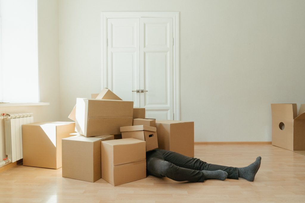 A man laying bellow the pile of boxes because he didn't follow packing hacks.