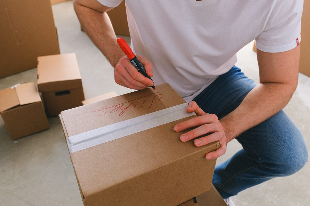 A man marking box with permanent marker following packing hacks.