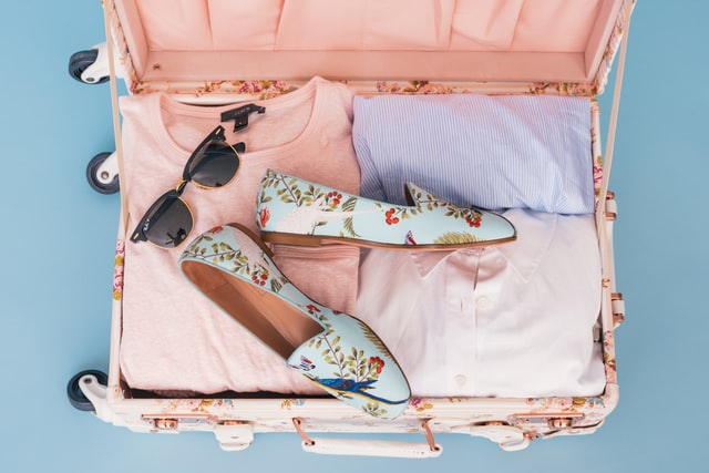 A woman packing your shoes and jackets in a suitcase.