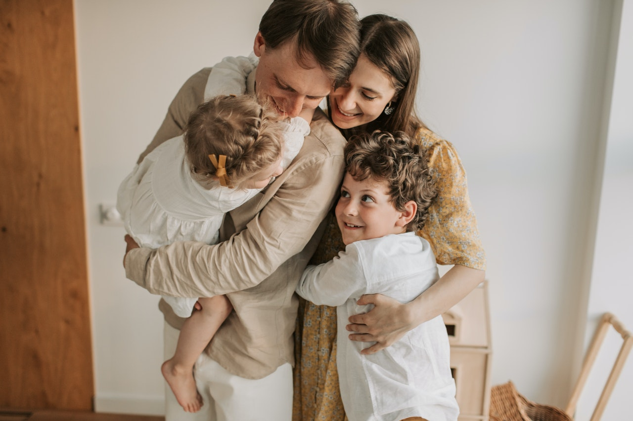 Husband, wife, and their children hugging and smiling
