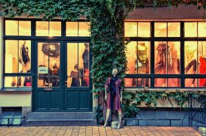 A doll dressed in a red dress placed outside of a boutique covered in plants