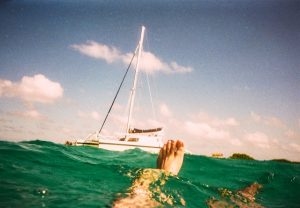 A yacht from the perspective of a man floating on water