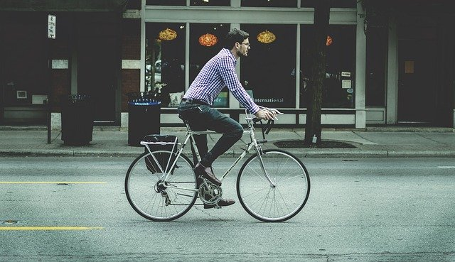 Man on a bicycle is choosing the location of your new home.