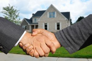 A handshake in front of a house.